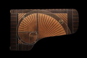 "STEINWAY & SONS MARKS A HISTORIC MILESTONE WITH THE UNVEILING OF THE COMPANY'S 600,000TH PIANO Renowned Designer Frank Pollaro Creates ""The Fibonacci,"" A Masterpiece That Celebrates The Art of Handcraftsmanship June 2015 – Steinway & Sons, manufacturer of the world's finest pianos, has unveiled the company's 600,000th piano, stunningly designed by master artisan, Frank Pollaro. Handcrafted using natural Macassar ebony, the end result is a feat of artistry, engineering and precision that celebrates this milestone for Steinway & Sons and demonstrates the company's ongoing commitment to uncompromising craftsmanship. Named ""The Fibonacci,"" the piano's veneer features the iconic Fibonacci spiral made entirely from six individual logs of Macassar Ebony, creating a fluid design that represents the geometric harmony found in nature. The lines of The Fibonacci spiral on the top of the piano's lid are projected down to its unique curved base. Synthetic ivory inlay adds a breath-taking effect to the design, which also features unique patinated bronze details. In the end, over 6,000 hours of work over a four-year period were devoted to the creation of The Fibonacci, from design to finish. The superior craftsmanship of the piano's exterior is matched only by the unparalleled craftsmanship that is at the very core of all Steinway & Sons pianos."